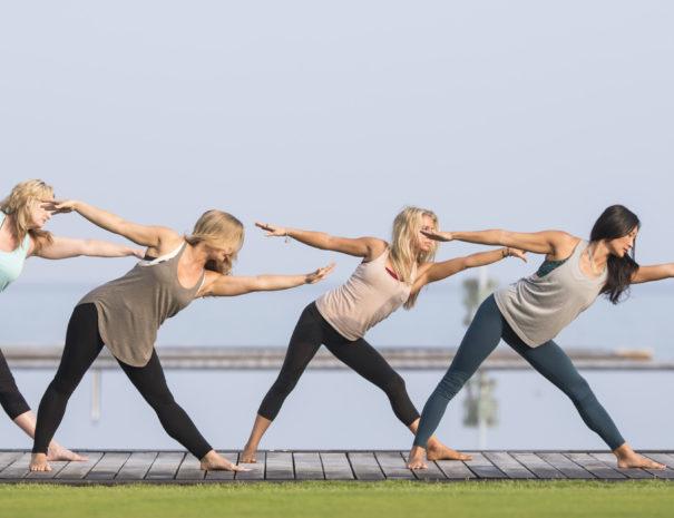 Four women in leggings doing synchronized stretching