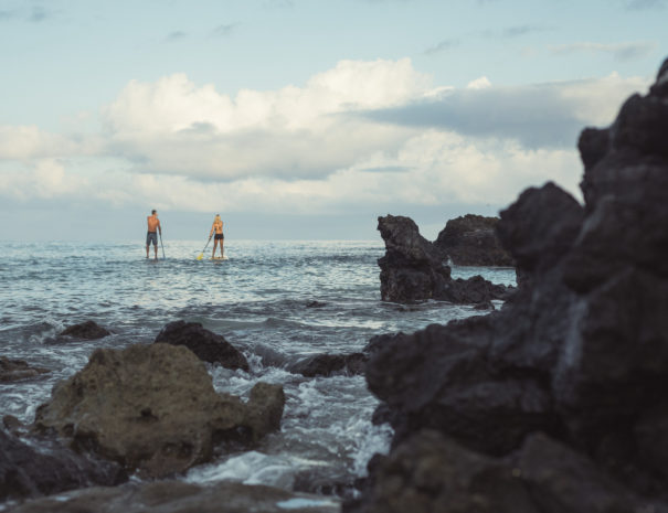 Man and woman paddle boarding past lava rocks in the ocean