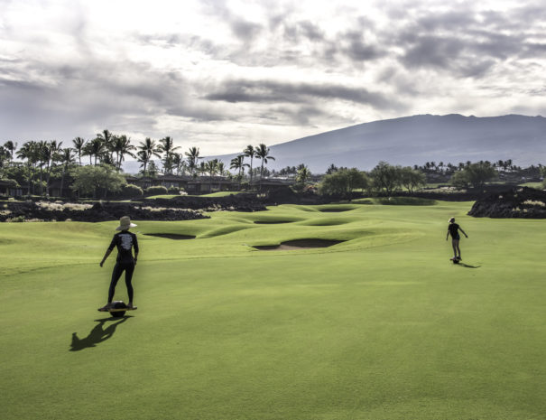 Two people Onewheel Turf Surfing on the Hualalai Golf Course with Hualalai mountain in the background