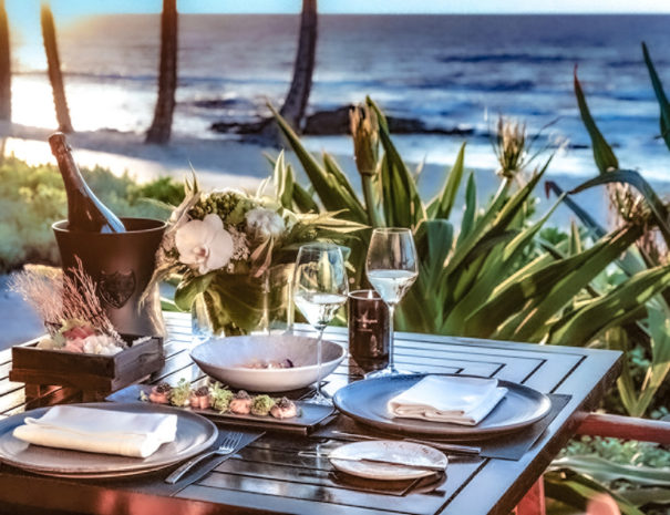 Place setting for two with champagne being chilled and trays of sushi with ocean background