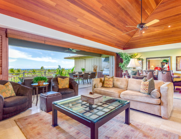 High ceilings above a comfortable living room area and dining table with views past open sliding doors to outdoor lanai and tropical landscape beyond