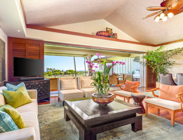 Living room with tan couch and bright pillows and four chairs surrounding a large coffee table and orchid plant and television behind