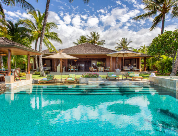 Beautiful private pool and spa next to outdoor eating area and lounge chairs with view into beautiful Laueki 8 rental home with Hualalai Villas and Homes