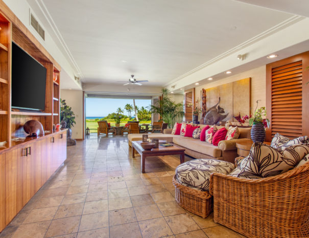 Tiled living room with Hawaiiana decorations on comfortable seating and facing a large entertainment center with art, books, and a large television. Golf course and ocean views in the background of open sliding door.