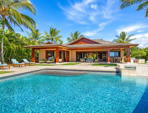Bright pool facing coconut trees and Pu'ukole home at Hualalai Resort