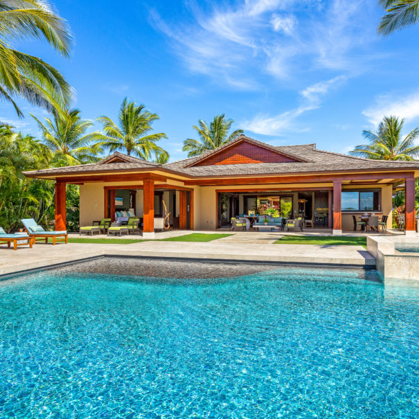 Bright pool facing coconut trees and Pu'ukole home at Hualalai Resort