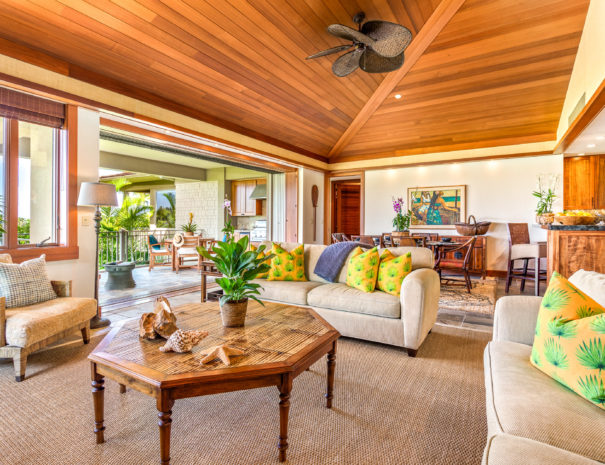 Comfortable living room with bright, multicolored pillows on couches with high ceilings and looking out toward lanai.