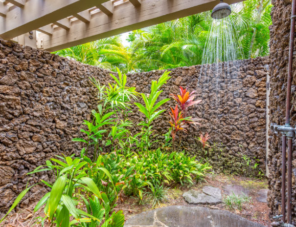 Rough lava rock wall with outdoor shower spraying water with tropical foliage