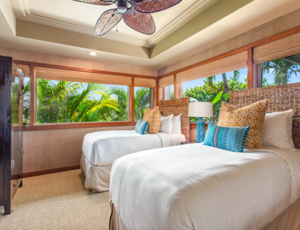Carpeted bedroom with two twin beds and textured wallpaper across from armoire surrounded by windows showing tops of palm trees.