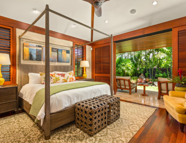 Colorful accent pillows match lamps and chair at the end of a comfortable bed with accent rug on wooden floors. Sliding doors open to show tiled lanai and outdoor furniture facing outward.