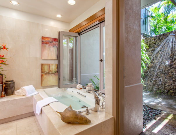 Large bath tub full of water with art on the tiled walls separated from an outdoor shower by an open door and window