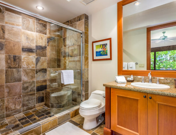 Tiled bathroom with walk in shower and sliding door next to toilet and sink with large mirror.