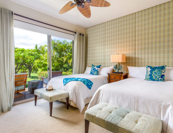 Two double beds and benches in front of patterned wallpaper and view outside of two chairs facing lush tropical surroundings