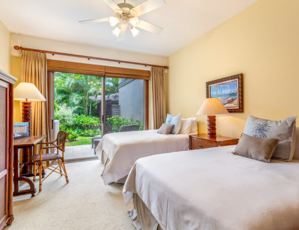 Carpeted guest room with two double beds facing a desk and entertainment center with outdoor furniture on lanai beyond sliding doors
