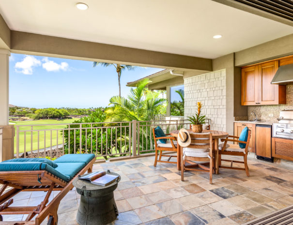 Outside lounge chair with teal pillows and side table with round table with four chairs next to outdoor cooking area on second floor lanai.