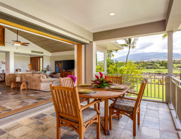 Wooden dining table with outdoor lanai with views of Hualalai mountain and sliding door open to view inside living room with high ceilings.