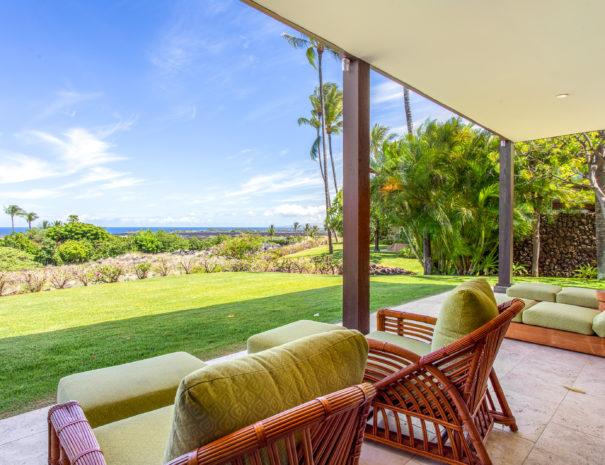 Outdoor furniture on tiled lanai facing grass and ocean