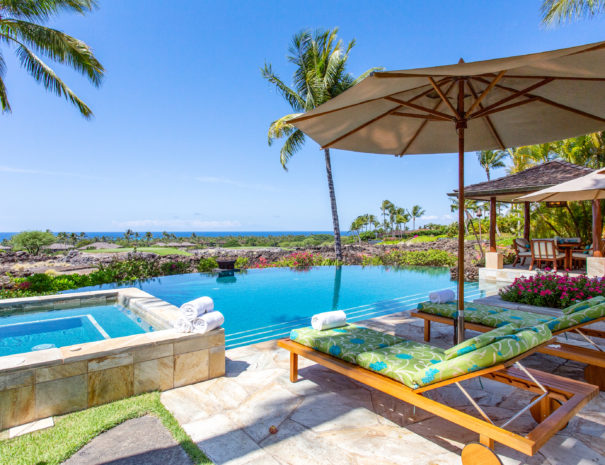 Blue skies, coconut trees, and Pacific ocean providing backdrop to beautiful infinity pool and spa with multicolored lounge chairs underneath a sun umbrella and outdoor dining area beyond.