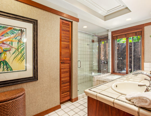 Tiled bathroom with double vanity facing wallpapered wall with art and cabinets next to a large walk in shower and bath tub.