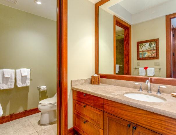 Tiled bathroom with door separating toilet and large vanity