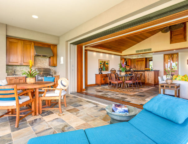 Tiled lanai with blue lounge chair, round table with chairs looking toward outdoor cooking area and inside to Waiulu Villa 133B.
