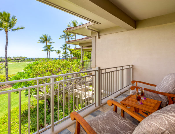 Two comfortable outdoor chairs with drinks on table between facing toward golf course and ocean views.