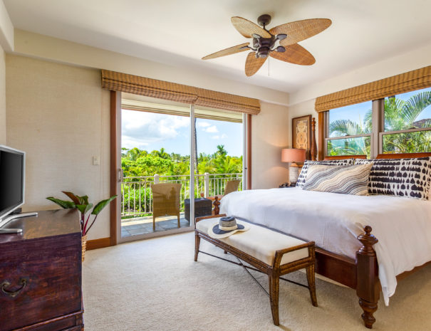 Upstairs carpeted guest bedroom with comfortable bed and bench facing small television and showing lush tropical greenery from windows and outdoor lanai