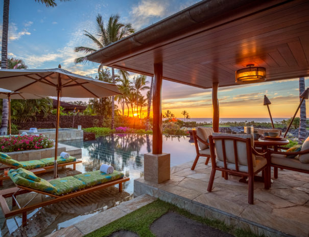Multicolored lounge chairs at luxurious private infinity pool and outdoor dining area with sun setting through coconut trees over the ocean at Hualalai Resort.