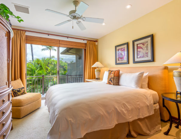 Carpeted bedroom with comfortable bed facing dresser and comfortable chair, the sliding door shows outdoor lanai and tropical foliage