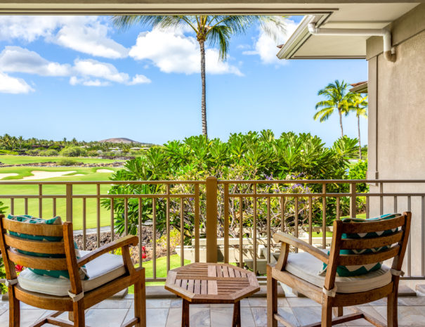 Two wooden chairs with cushions facing out to Hualalai Resort view from second floor, tiled lanai.