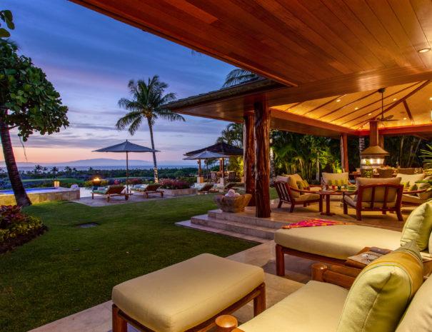 Comfortable, outdoor furniture on tiled lanai looking toward private pool and views of Hualalai at dusk