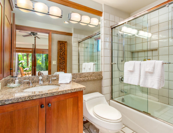 Tiled bathroom with sliding glass doors on tub, toilet, and single vanity with mirror reflecting ar ton wall papered walls and open door leading to bedroom.