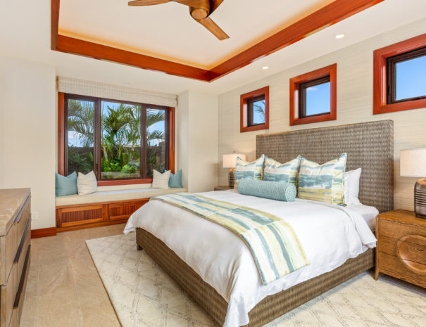 Large bed with sitting nook with large window and palms