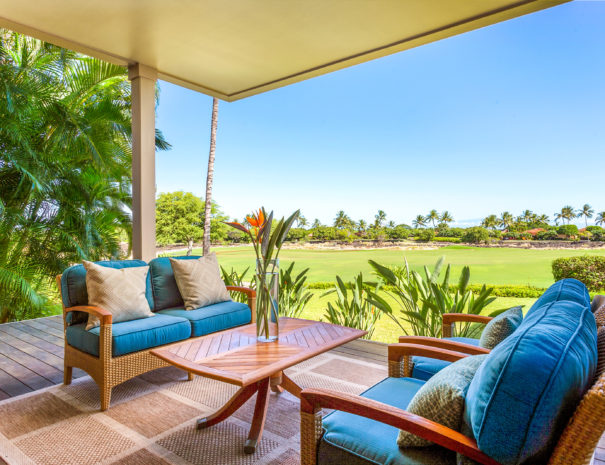 Comfortable outdoor furniture facing small table on outdoor lanai with views of golf course beyond
