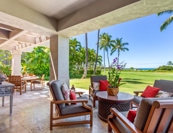 Tiled outdoor lanai with four comfortable chairs around a circular table with flowers on it show a beautiful tropical view of golf course, coconut trees, and the ocean.