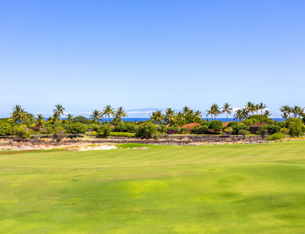 Hualalai Golf Course with ocean past coconut trees and island of Maui peeking over the clouds in the distance
