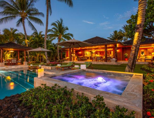 Laueki private spa and pool lit up at dusk facing lit up house at Hualalai Resort with Hualalai Villas and Homes.