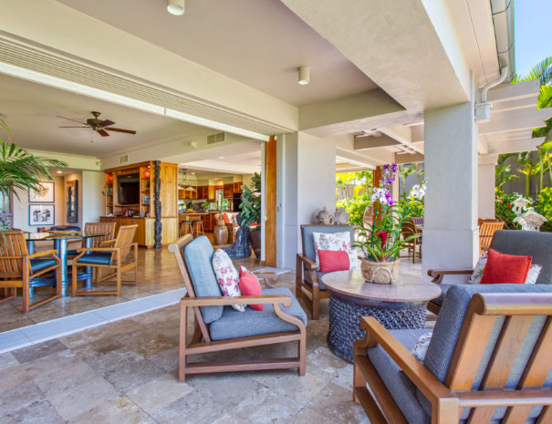 View inside a home from the outside lanai showing outdoor seating as well as indoor living area and kitchen in the background.