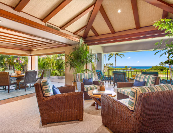High wall papered ceilings with wooden beams over a carpeted living area with four chairs surrounding a circular coffee table, showing two outdoor balconies with dining table on one and seating area on another.
