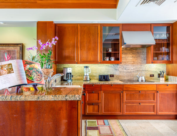 Inviting and well equipped kitchen with recipe book open on a stand and wooden cabinetry and marble countertops