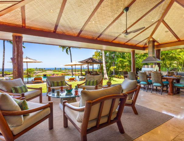 Luxurious outdoor living space with plenty of comfortable seating and dining area with views of the ocean beyond
