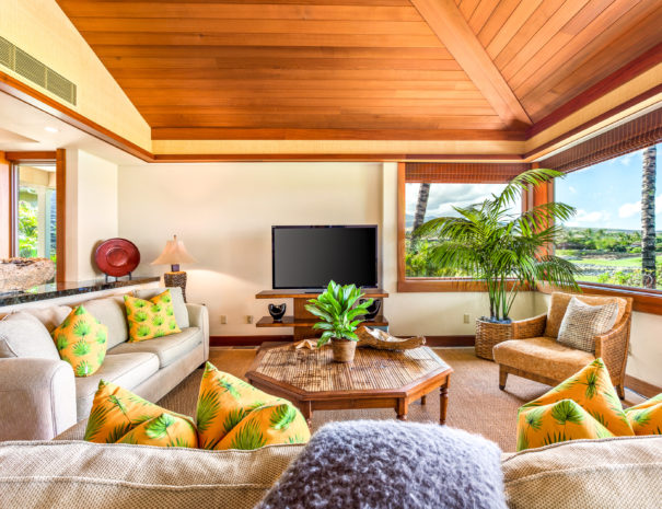 Living room with comfrotable couches and large multicolored pillows facing a television with large windows showing golf courses, lava rocks, and views of Hualalai.