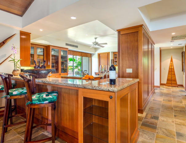 Three bar stools under marble counter with wine, art, and orchids with kitchen in the background.