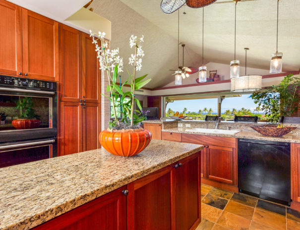 Tiled kitchen area with marble counter tops and wooden cabinetry looking past large orchid plant to oven and dishwasher towards tropical view outside