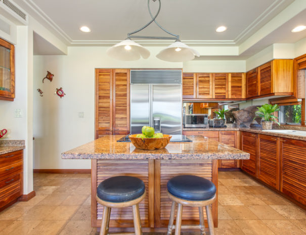 Tiled kitchen with large marble lanai and koa cabinetry and stainless steel appliances.