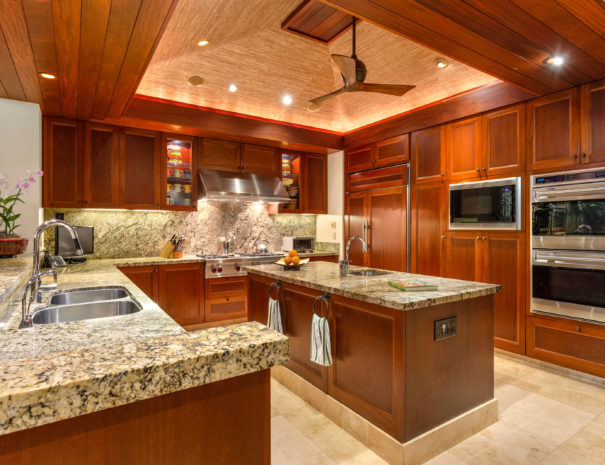 Beautiful well appointed kitchen with marble counter tops and wooden cabinetry and custom woven high ceilings