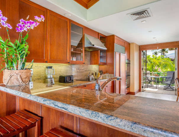 View over a marble kitchen bar to well appointed kitchen and open doors to outdoor lanai beyond
