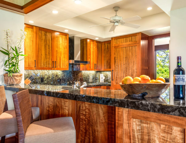 Two bar stools, a fruit bowl, and wine on a marble bar top with beautiful wooden cabinets above a well appointed kitchen.