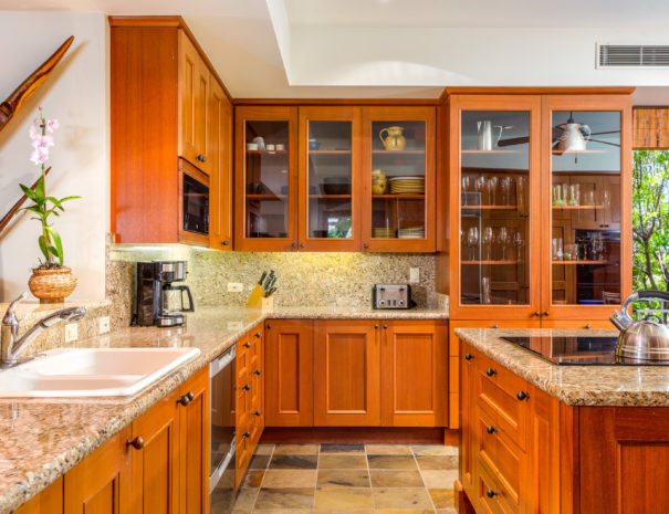 Tiled kitchen with marble countertops, wood and glass cabinetry, and large island with induction stove.