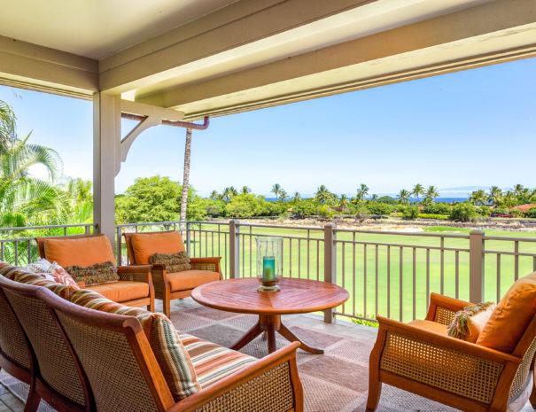 Comfortable seating surrounding circular table on an outdoor lanai facing toward golf course and ocean views at Hualalai Resort